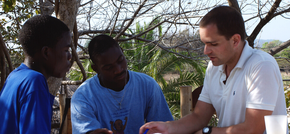 Matt, a volunteer teacher, holding an afternoon tutorial at Mwaya Beach