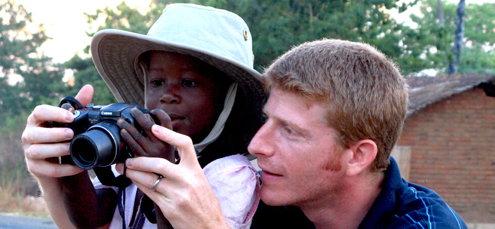 Marc showing a local child how to take a photo