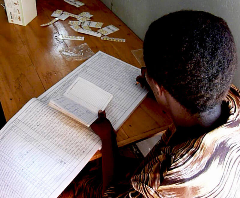 A medical volunteer records data in the clinic book in Malawi