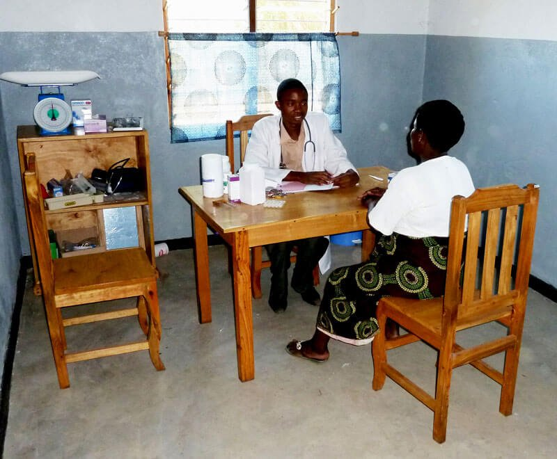 A medical assistant attends to a patient in Malawi