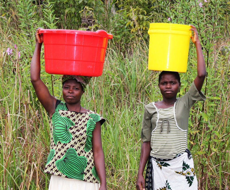 Two women carry buckets of water on their heads in Africa