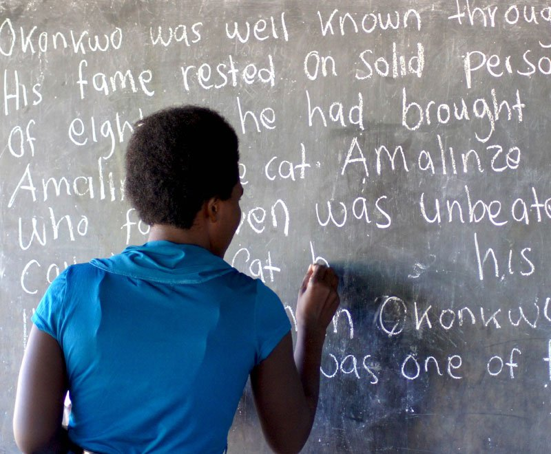 African adult literacy teacher writes on the board in Malawi