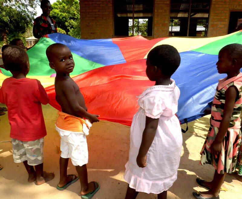 Children play with a parachute at preschool in Malawi