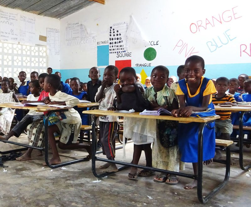 Children sit happily at their newly donated desks