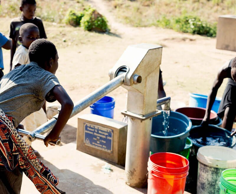 Fresh water being pumped from a borehole in rural Malawi