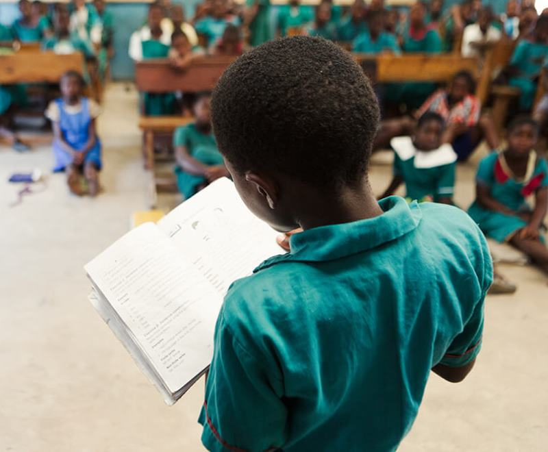 A primary school student reads to his class in Africa