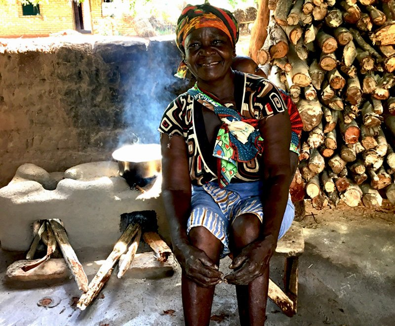 Empowering Kettie means she has built and maintains her fuel efficient cookstove in her kitchen in Malawi