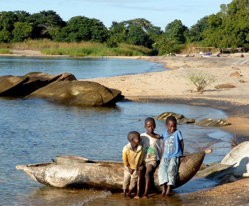Children rest on a canoe in Africa