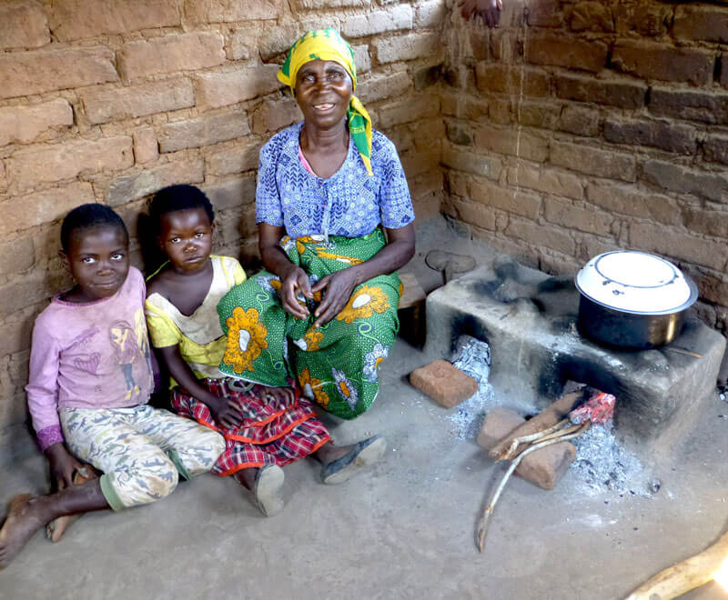 Family sitting by their fuel efficient cookstove in Malawi