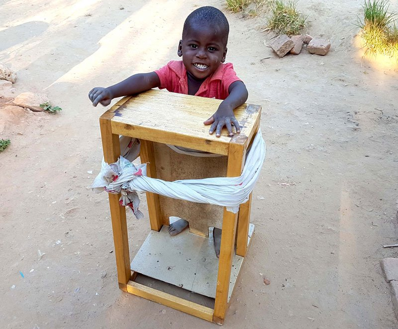 This little boy has cerebral palsy but is learning to stand in a standing frame in Malawi