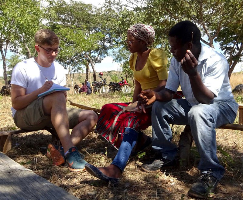 International development student volunteer meeting with forest conservation beneficiary in Africa