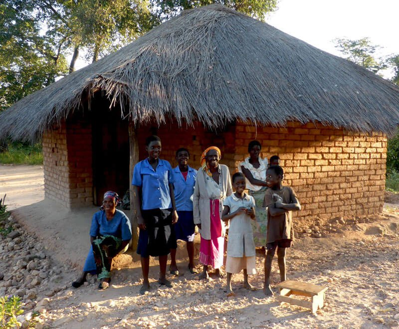 A rural Malawi home with the family smiling outside