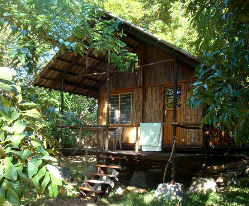 Wooden volunteer chalet nestled in the trees in Malawi