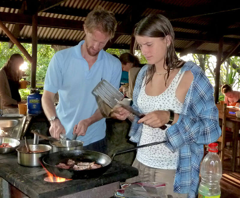 Ripple Africa volunteers prepare breakfast on a wood burning stove