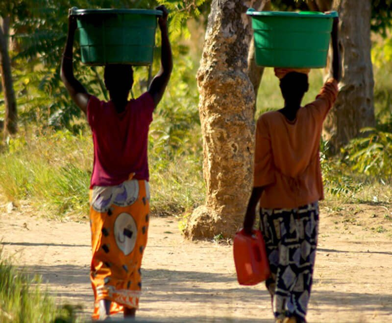 Two women walk home from the borehole with their water in Africa