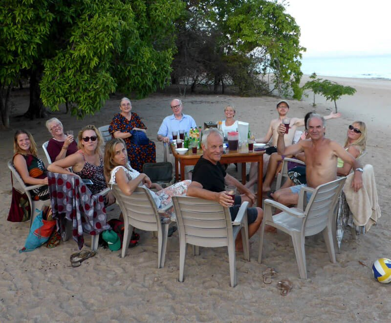 A group of volunteers enjoy the weekend with drinks on the beach