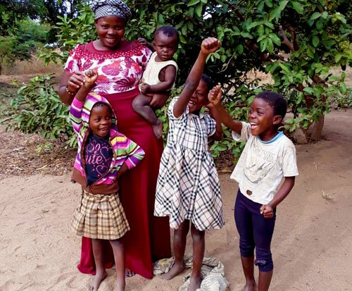 Malawian mother smiles happily with her children