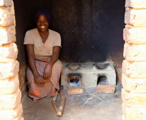 Glory sits with her fuel efficient cookstove in Malawi