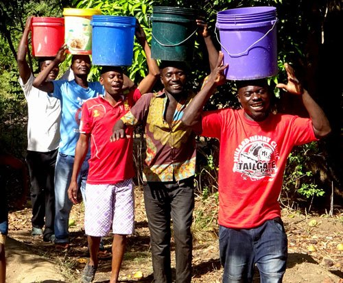 Men carry water in Malawi to help their wives