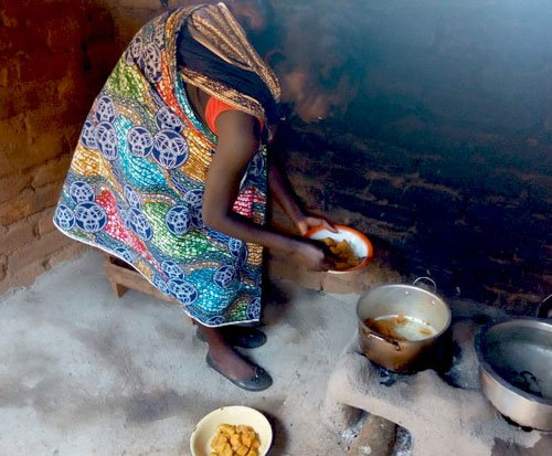 A Malawian woman cooks sweet potato on her fuel-efficient cookstove in Malawi
