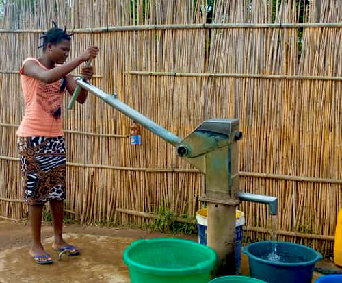 A young woman pumps water from a borehole in Malawi