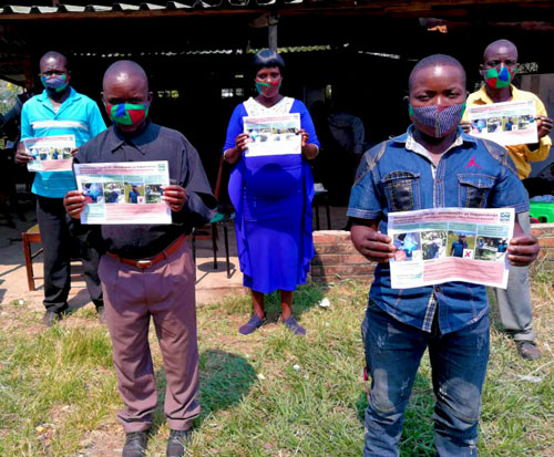 Fish conservation committee members with awareness posters and masks in Malawi